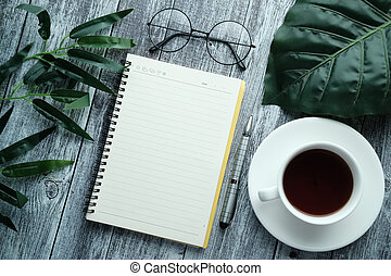 Top view of open notepad , tea and pen on table.