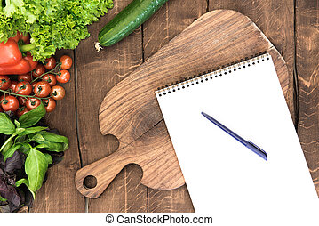 Top view of organic vegetables, chopping board and blank notepad with pen on wooden background