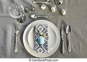 top view of painted blue chicken egg on plates on festive table