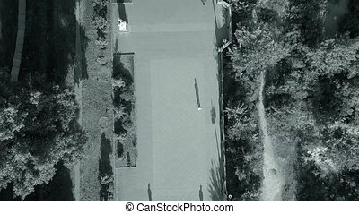 drone flying over people walking in the park at sunset time with long shadows black white video