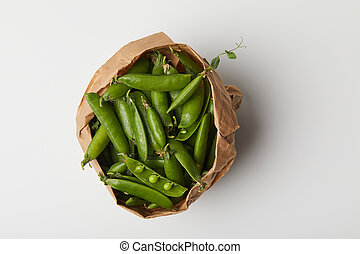 top view of pea pods in paper bag on white surface