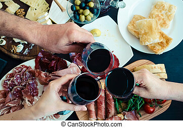 Top view of people toasting with glasses of red wine
