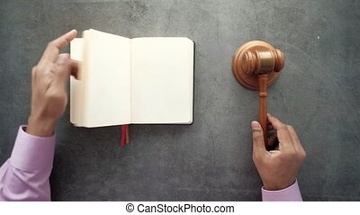 top view of person's hand striking the gavel .