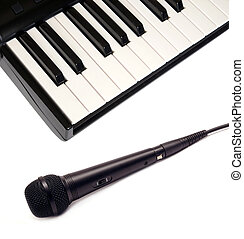 Top view of piano keyboard and black vocal microphone on white background closeup