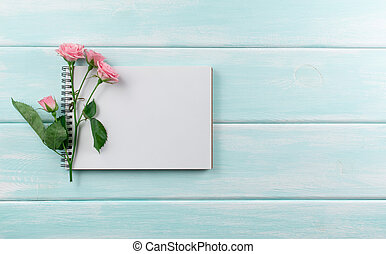 Pink roses and empty notebook with place for text on wooden background. Top view. Flat lay style.