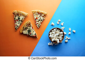 top view of pizza, popcorn on color background.