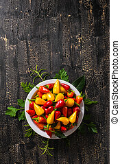 top view of plate with orange, red and yellow hot chili peppers, greenery on cracks black background, close up