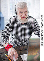 Top view of pleasant elderly man enjoying online games