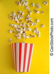 top view of popcorn spilling on yellow background