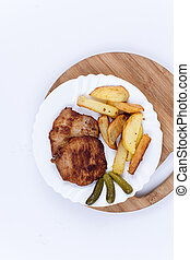 Top view of pork chops with french fries on the plate