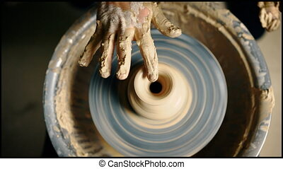Top view of potter hands working on pottery wheel and making...