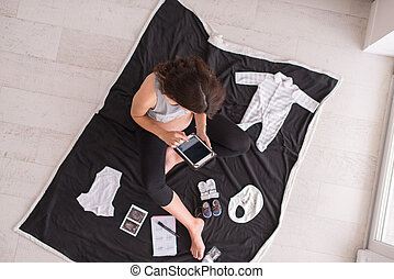 top view of pregnant woman checking list of baby clothes