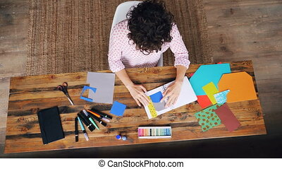 Top view of professional designer working at table making paper collage sticking figures in notebook and cutting shapes with scissors. Workplace and creativity concept.
