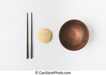 top view of raw rice heap with bowl and chopsticks on white