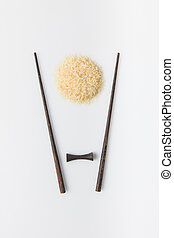 top view of raw rice with chopsticks on white