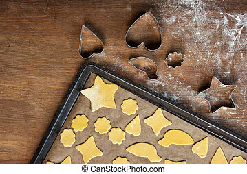 top view of raw shaped cookies on baking tray and cookie cutters on wooden table