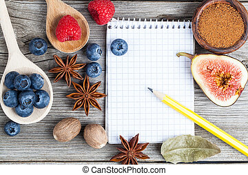 top view of recipe book with ingredients on wooden table