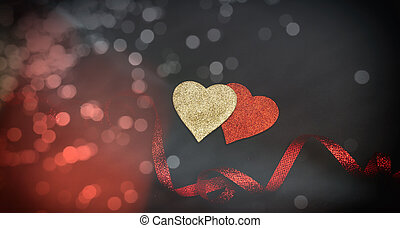 Top view of red and golden hearts with ribbon, black background, bokeh.