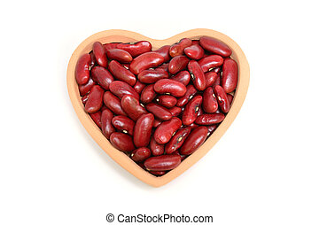 Top view of red beans in wooden heart isolated on white background
