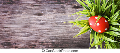 Top view of red easter egg in grass nest on vintage wooden background.
