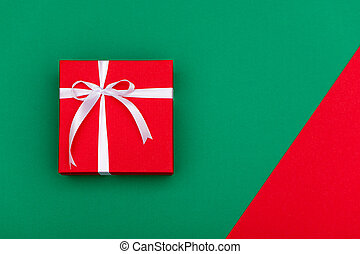 Top view of red gift box with white ribbon on green background