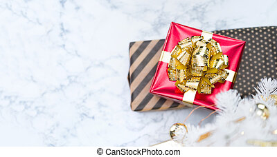 Top view of red glossy present box with golden bow and ribbon lay under white christmas tree on white marble floor, Holiday gift giving banner, leave space for adding text.