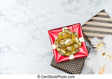 Top view of red glossy present box with golden bow and ribbon lay under white christmas tree on white marble floor, Holiday gift giving, leave space for adding text.