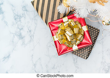 Top view of red glossy present box with golden bow and ribbon lay under white christmas tree on white marble floor, Holiday gift giving, leave space for adding text