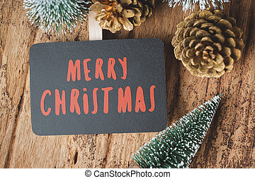 Top view of red Merry Christmas blackboard with xmas tree and gold pine cone on grunge wood table .winter holiday greeting card.