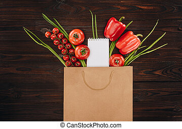 top view of red tomatoes and bell peppers with empty notebook on wooden table, grocery concept