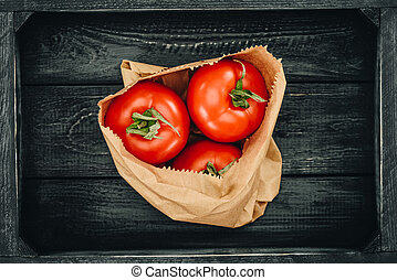 top view of red tomatoes in shopping paper bag, grocery concept