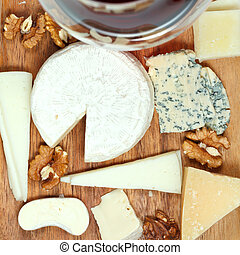 top view of red wine glass and assorted cheeses