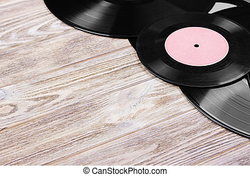 Top view of retro vinyl records over wooden background. Copy space for text