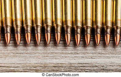 Top view of rifle full metal jacket bullets in a row on wooden background with copy space