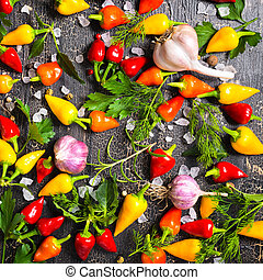 top view of ripe yellow, red hot chili peppers, sea salt, different greenery, black peppers and garlic on cracks black background, close up