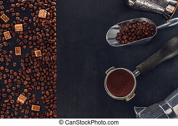 top view of roasted coffee beans, sugar, scoop, coffee tamper, coffee pot and coffee maker on black