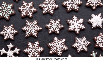 top view of rotating gingerbread cookies (snowflakes) on slate table