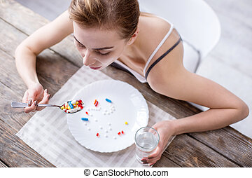 Top view of sad young woman sitting at the table