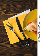 top view of sandwich on yellow plate with fork and knife
