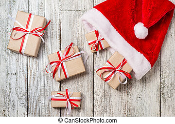 Top view of santa hat with christmas gift boxes on white wooden background