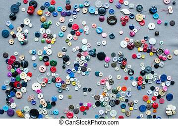 top view of scattered colorful buttons on grey cloth background