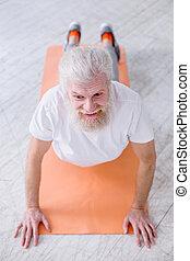 Top view of senior man standing in upward-facing dog pose