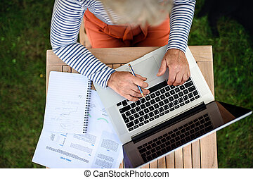 Top view of senior woman with laptop working outdoors in garden, home office concept.