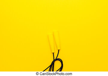 top view of skipping rope on yellow background with copy space