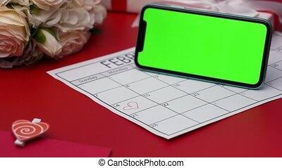 Top view of smartphone with green screen chroma key on red table in horizontal position. Romantic background with a calendar in which February 14 is surrounded by a red heart. Close up. Slow motion.