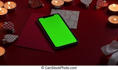 Top view of smartphone with green screen chroma key on red table with burning candles, hearts, valentine and gift . Romantic twilight background with lights. Valentine's Day. Close up. Slow motion.