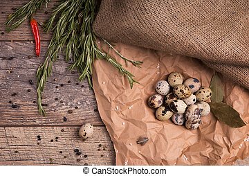 Top view of speckled quail eggs, bay leaves, rosemary, red spicy chili pepper and seasonings on a light background.