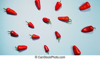Top view of spicy red chili peppers. Little red peppers. Chaotically scattered on a blue background. Copy space. High quality 4k footage