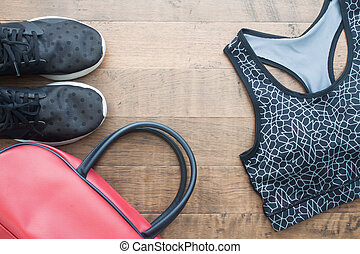 Top view of sport woman items on wooden background, Sport shoes, sport bra and bag