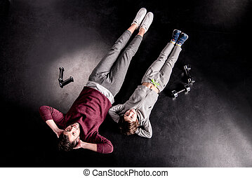 Top view of sporty father and son lying with hands behind heads